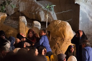A church worker (in blue) restrains a women screaming and thrashing violently during the Cave Church service.